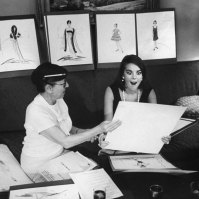 """Natalie's big brown-black eyes grow larger with delight seeing costumes sketched by Edith Head for Sex and the Single Girl."""