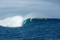 Kohl Christensen and other surfers take off on a set wave, Cloudbreak, Fiji.