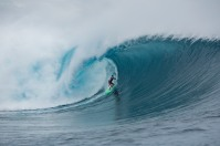 A surfer from Brazil rides deep inside a wave in Fiji.