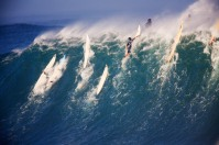 A huge wave breaks deep over the rocky reef as surfers barely scrape over the wave, Waimea Bay, Oahu, Hawaii.