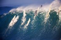 A huge wave breaks deep over the rocky reef as surfers barely scrape over the wave, Waimea Bay, Oahu, Hawaii.
