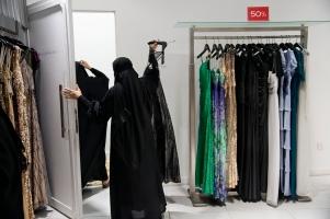 Μια πωλήτρια βοηθά έναν πελάτη να επιλέξει ένα φόρεμα σε κατάστημα του εμπορικού κέντρου Al Faisaliyah.